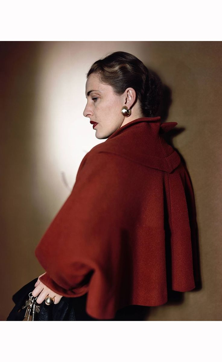 Slim Keith. She is wearing a red bolero capelet by Trigere, over a black sheath dress, Her back is facing toward the camera, showing the line of the jacket.
