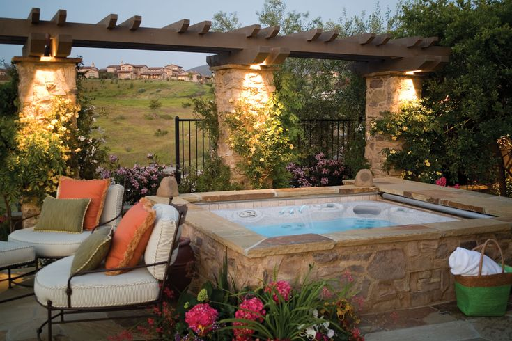 Make your backyard beautiful by surrounding a #HotSpringSpas hot tub with natural stone! This natural stone matches the light-colored stone columns.
