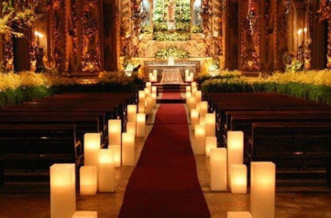 Square candle luminaries light up the aisle of this beautiful church for a spectacular wedding