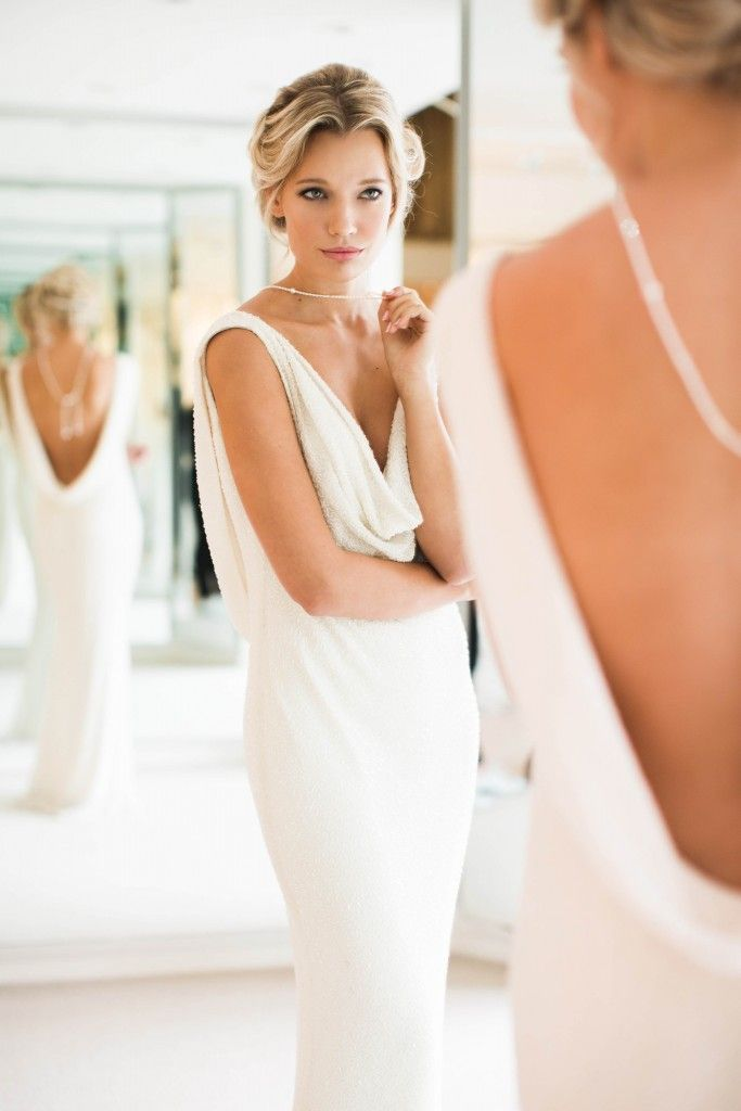 With a dramatic cowl neck and deep scoop back, this modern twist by Joyce Young on the 1970s Grecian-style evening gown makes a great choice for beach or evening celebrations where you want to create maximum impact without traditional accessories but still crave the classic long white wedding dress. More at http://absolutely-weddings.co.uk/classic-white-wedding-dresses/