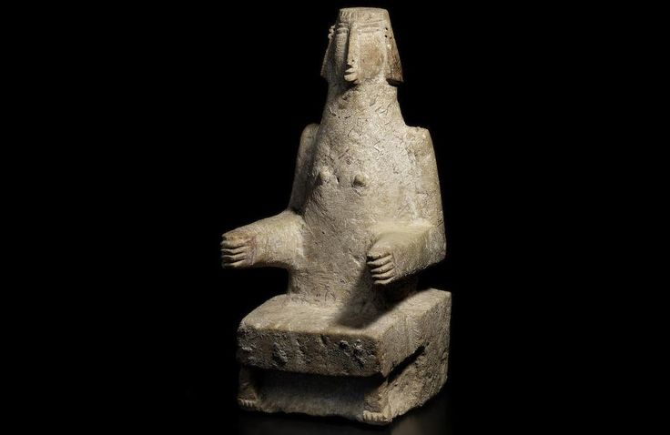 South Arabian limestone seated female figure, 7th-6th Century B.C. Depicted facing frontally, seated on a block stool, her feet showing at the bottom of her dress, her arms bent at the elbow with the forearms reaching forward, with small breasts, her stylised face with small pouting mouth and a long nose, her ears pierced and her hair with cross-hatched incised detail, 27.3 cm high. Private collection