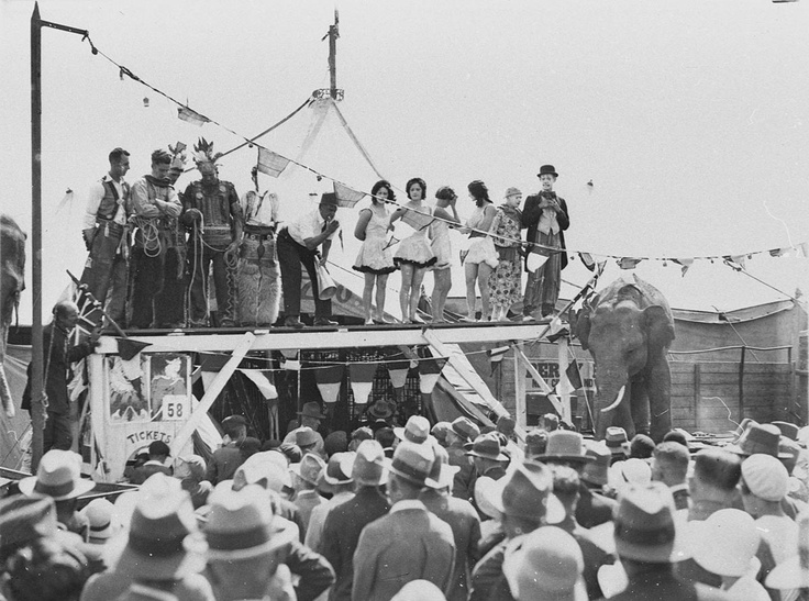 """Clowns, """"Indians"""", girls and spruiker at sideshow, Sydney Royal Easter Show, 1930s"""