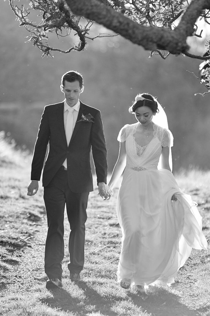 Black and white shot of bride and groom walking, beautifully back-lit. Captured by Adam Popovic Photography. Auckland wedding photographer.