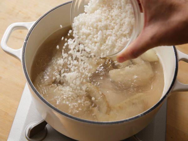 鍋に水、②の鶏肉、にんにく、しょうがを入れ、沸騰したら米を加える