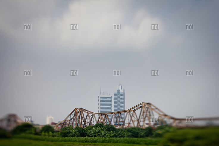 [photo by Francis Roux] Old meets new. Modern high rises tower behind Long Bien bridge in Hanoi, Vietnam