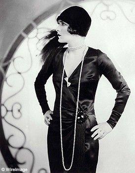 On y voit une femme dans les années 20, habillé en robe du soir. La robe est cintrée, et elles ne portent plus le corset. Elle porte une robe noire, en satin, très simple, des gants et un chapeau pour l'élégance. Les femmes dans ces années étaient très classe, avaient beaucoup d'élégance. (Publier par Clara Fourrier)