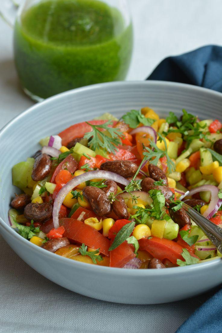 Kruidig gebakken kievitsbonen, zoete gegrilde paprika, maïs en selderij maken samen met een groene kruidenolie een vrolijke en voedzame bonensalade.
