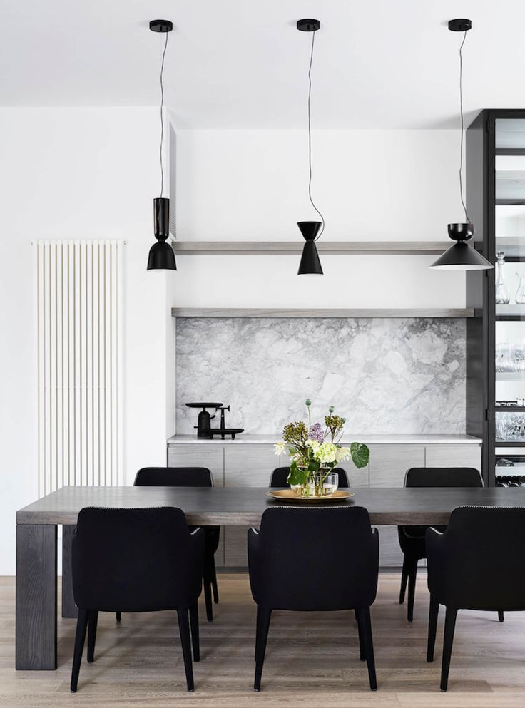 Monochrome dining room with joinery: light grey marble splashback, grey veneer cabinets, marble benchtop, grey veneer thick floating shelves, three mismatched black pendant lights, wooden rectangular dining table, black upholstered dining chairs, timber floorboards, flowers in glass vase