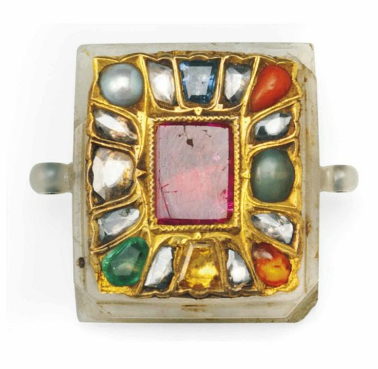 A DIAMOND-SET JADE PENDANT (NAVRATNA)  NORTH INDIA OR DECCAN, 19TH CENTURY  Of rectangular form, the reverse with beveled borders, with two carved hanging loops, set in gold with the nine typical gems and pearl, the jade chipped 1 3/8in. (3.4cm.) across