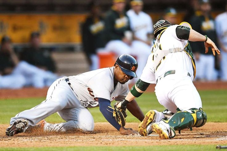 Beats the tag:     Justin Upton #8 of the Detroit Tigers scores beating the tag of Stephen Vogt #21 of the Oakland Athletics in the top of the fourth inning at O.co Coliseum on May 27, in Oakland, Calif.