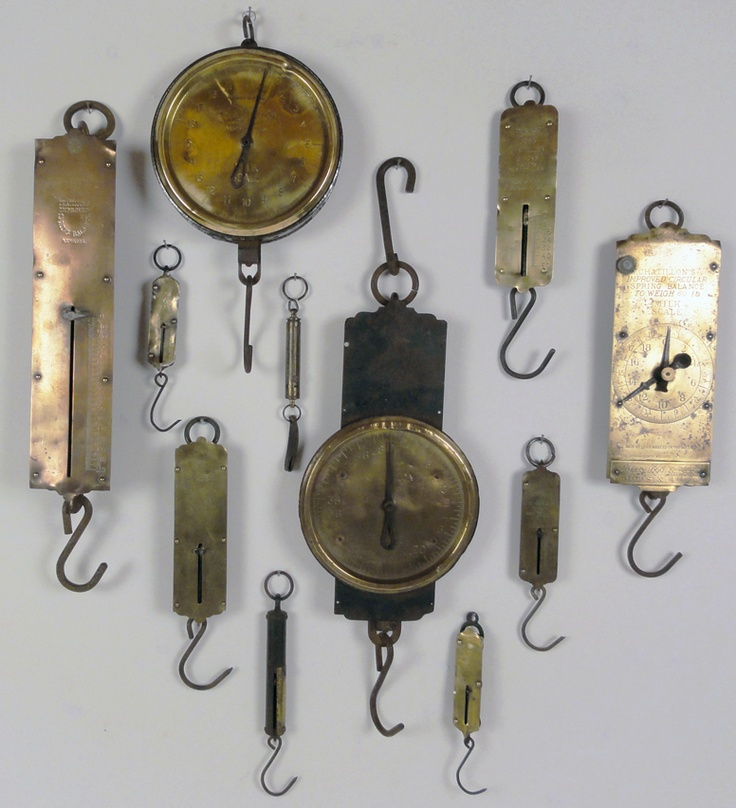 "Antique Brass Scales.   A collection of 11 antique hanging brass milk scales ranging in size from 9"" to 21 1/2"" (including the hooks and rings). Great for a kitchen or restaurant display."