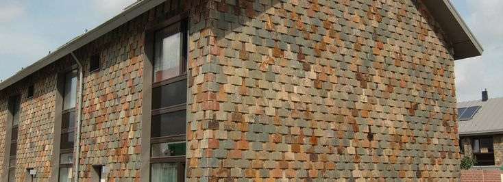 Natuurleien gevelbekleding bijna als 'schubben' aan de woning geven een levendige kleur en reliëf.