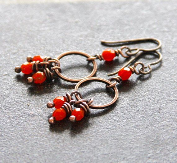 A trio of bright opal orange faceted Czech glass beads are wire wrapped in oxidized copper and dangled below small copper rings. All swing below the same Czech glass bead. The copper is buffed and the earrings are finished with hypoallergenic niobium ear wires. The earrings hang