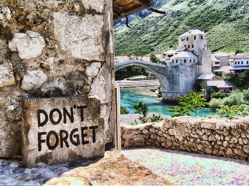 Mostar, Bosnia. If you tip them 25 Convertible Marks, Bosnian divers will take the 20 m plunge into the icy cold river. The sign is a reminder of the atrocious war of the mid 1990's