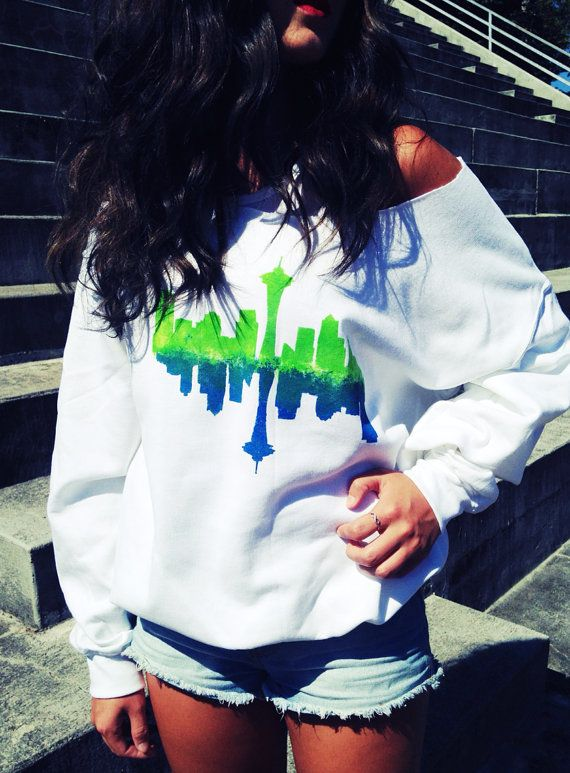 $35 White off the shoulder Seahawks colored Seattle skyline sweatshirt. Mens sizes small-large, meant to fit baggy, model is wearing a small. Www.hawkout.etsy.com