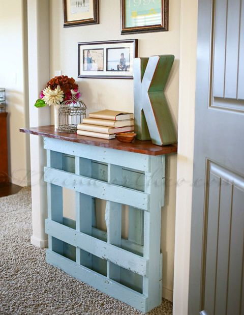 A maple-stained board atop a chalk-painted pallet becomes the perfect platform for your living room odds and ends. See more here.