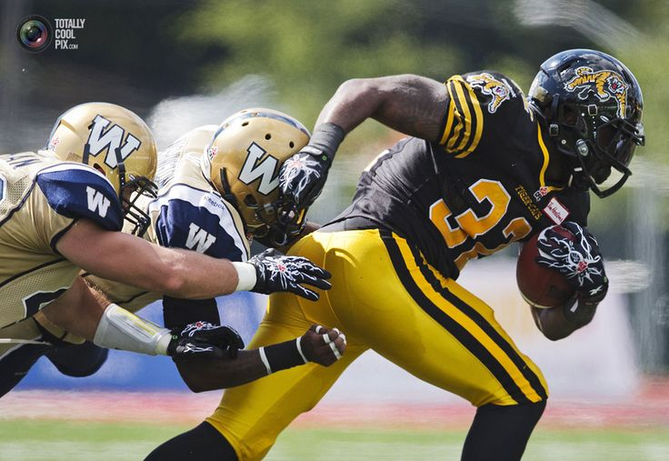 Coolest Sports Pix Of 2013 Week 34 - Tiger-Cats Gable breaks the tackle of Blue Bombers Washington and Stephen during their CFL football game in Toronto. MARK BLINCH/REUTERS