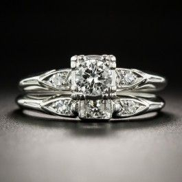Although weighing just over one-third-carat, the sparkling center stone in this crisp, original vintage wedding set presents considerably larger, due to the artfully designed illusion setting. The scintillating stone radiates between sleekly stylized, elongated, diamond-set heart motifs which are mirrored in the matching wedding band. Beautifully designed and rendered in platinum, circa 1940s-50s, the soft knife-edge ring shanks are currently size 6 3/4.