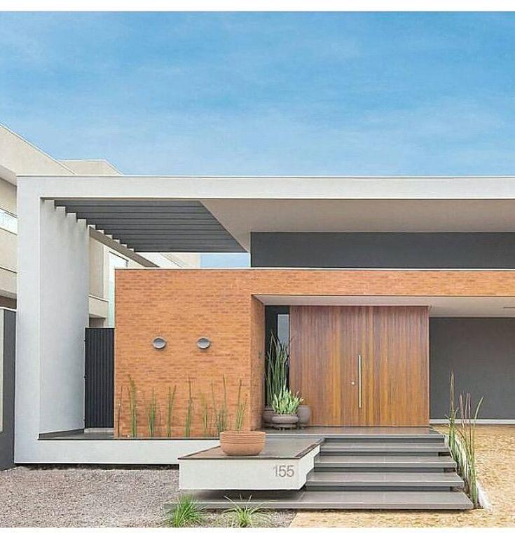 Com base retangular, pergolado na área lateral, porta de madeira e tijolos aparentes na fachada.
