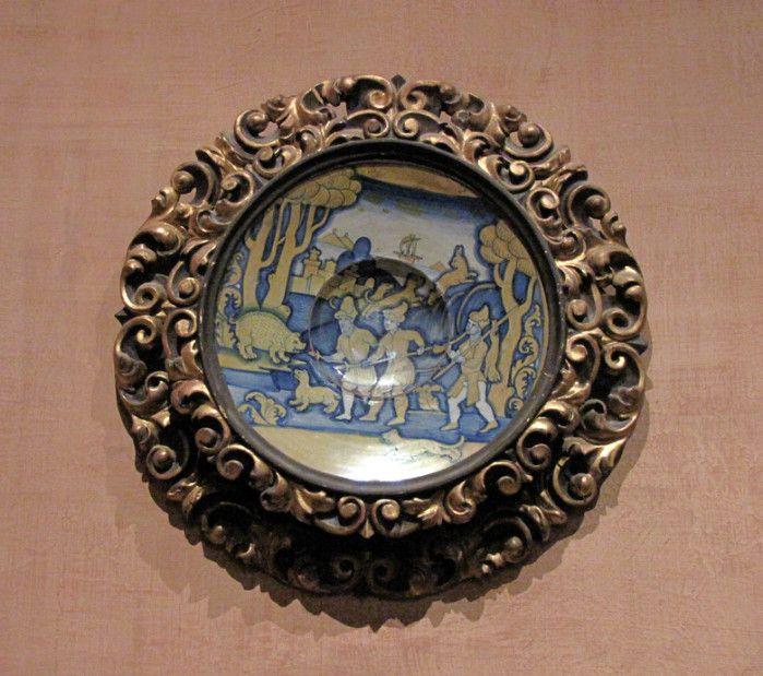Chateau-Ecouen-  * 1° majolique: Assiette présentant une scène de chasse.- Sur le mur son accrochées plusieurs majoliques encadrées, selon une habitude attestée en France au moins au XVII°s. Une assiette (E.CL.2038) représente une Scène de chasse, inspirée probablement d'une gravure florentine. Elle est caractéristique par sa bichromie, or et bleu, de la production de GIACOMO MANCICI dit EL FRATE, à Deruta dans les années 1540-1545.