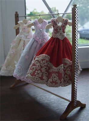 1/12th scale dress rail with collection of silk dresses.