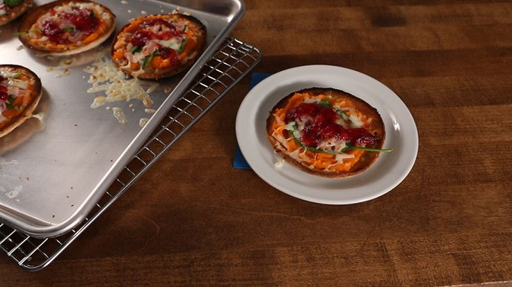 "In these unique ""pizzas,"" mashed sweet potatoes stand in for the marinara sauce, while thin whole wheat sandwich rolls act as the crust (a pita or tortilla would also work well). Add a handful of spinach for extra vitamins and a drizzle of warm cranberry sauce for color and flavor."