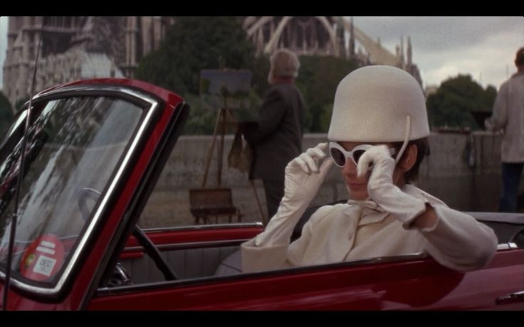 Adjusting her shades on the Pont de la Tournelle, in front of Notre Dame Cathedral. Other landmarks in How to Steal a Million include the Cathédrale de Notre Dame and the Hôtel Ritz. The Cathedral looms behind Hepburn as she drives along the Pont de la Tournelle, decked out in white driving hat and shades. Her outfit is slightly less chic, later, when she gives Peter O'Toole's character a ride to the Ritz (she has her night gown on underneath her jacket)…