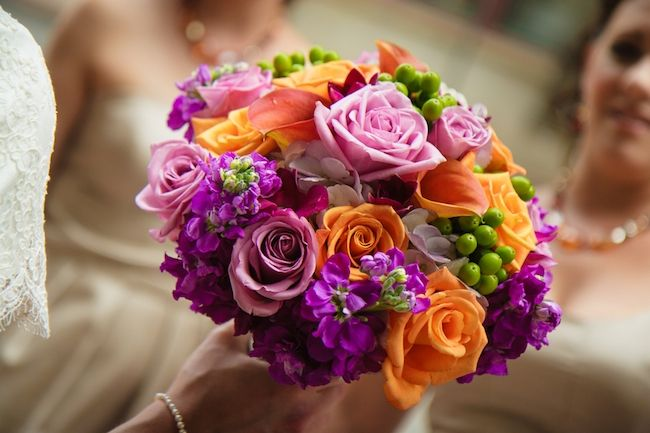 Colorful bridal bouquet in shades of fuchsia, orange, and purple. Photo by Studio Chyree