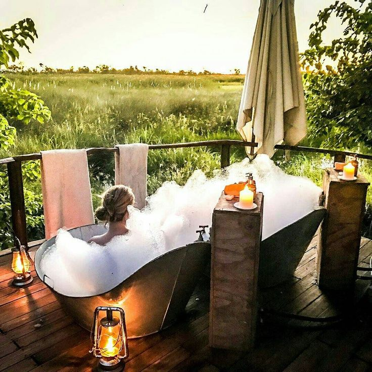 """Loving this stunning shot taken by @emtaneva at Sanctuary Baines' Camp. Definitely the best way to finish a day on safari.  ... """"Admiring the #sunset after a long game drive at the Okavango Delta#magical #escape #relax #wilderness . . . #lodge #cabinlife #nature #outdoor #bubblebath #bubbles #bathtub #cabin #loghome #travel #wanderlust #safari #africa #bostwana #luxury #luxurysafari #instafollow #beautiful #love #house #modernoutdoor #discoverearth #travelgram #nakedplanet"""""""