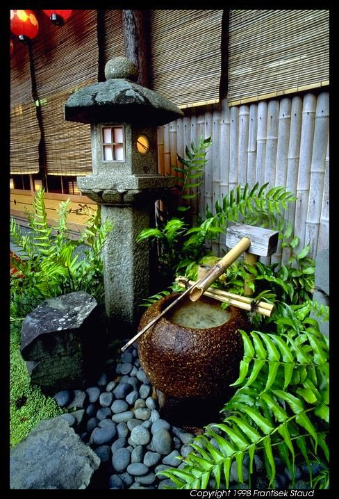 Stone lantern, rustic stone water well, a beautiful old rock, river rocks, and simple ferns to add softness and green.
