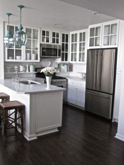 """I love this small kitchen! Tips on making a small kitchen feel bigger. """"Replace solid cabinet doors with glass ones. Glass fronts lighten the look of cabinetry and allow the eye to travel through to the back, which helps the kitchen seem more expansive. Just don't clutter the interiors with bric-a-brac — you'll defeat the purpose."""""""