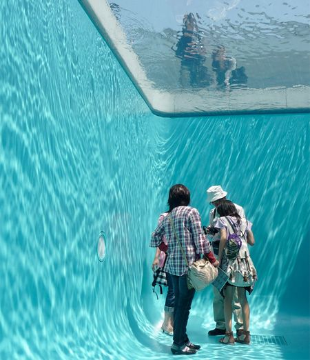 Creative art installation by Leandro Erlich features what appears to be a real swimming pool with people walking beneath the surface of the water.    To make the illusion, thin layer of water (only 10 cm deep) was suspended over glass. Below the glass, there is an empty room that visitors can enter. Fake swimming pools were installed at the PS1 Art Center in New Yorkand the 21st Century Art Museum in Kanazawa, Japan.