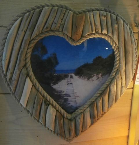 A lovely beach-themed driftwood photo frame - in the shape of a heart.  A number of pieces of driftwood have been placed around the edge to form the shape of the heart and two layers of rope have been added to the outer and inner edge to complete the effect.  You can put your favourite photo inside the frame. http://www.driftwoodartskiathos.com/portfolio/wall-hanging-decorations/heart-shaped-driftwood-photo-frame-1