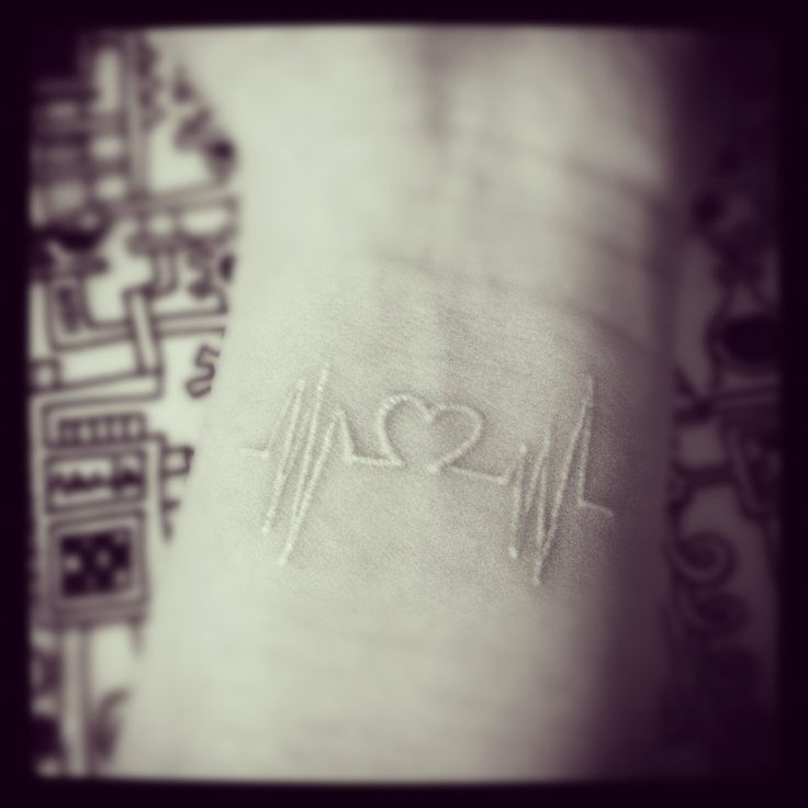 Heartbeat tattoo in white ink.