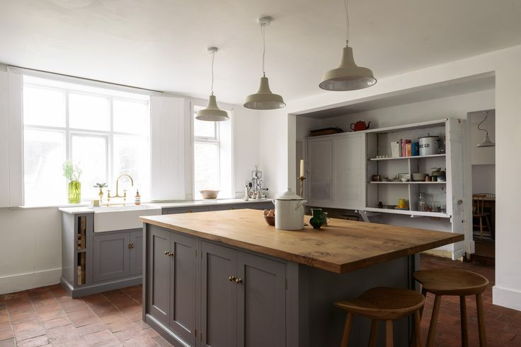 A beautiful central island with rustic oaks worktops, brass hardware a few simple pendant lights hanging above