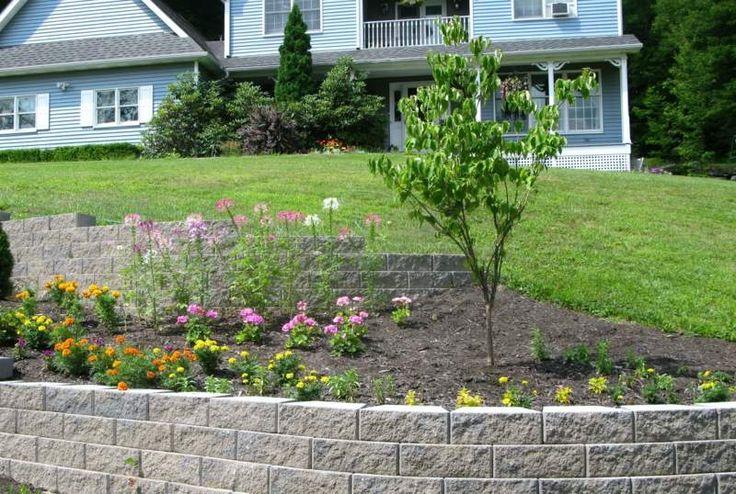 Durch die Stützmauer wird dem Hang eine Terrasse als Blumenbeet - hanglage pflegeleicht machen