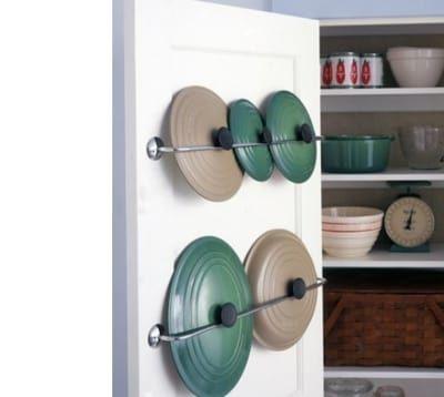 Instale suportes de toalhas de metal do lado de dentro da porta da despensa para penduras as tampas de suas panelas e dobrar o espaço de seus armários.