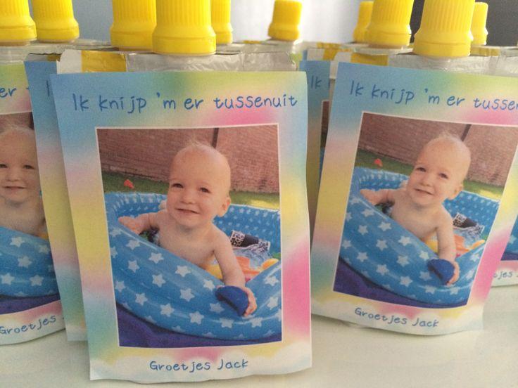 Afscheidstraktatie voor het kinderdagverblijf. Knijpfruit met een foto en tekst erop geplakt: Ik knijp 'm er tussenuit.
