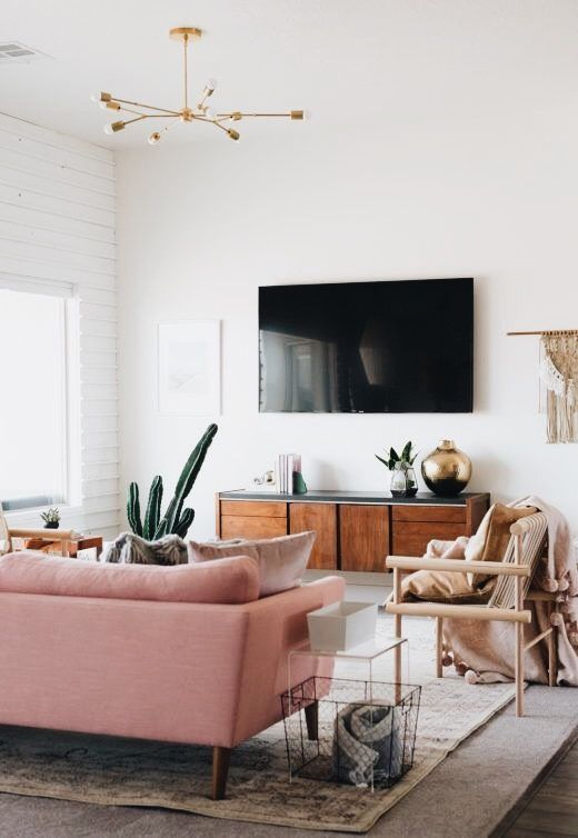 living room with pink sofa and modern accents, brass sputnik chandelier lends a very modern feel to the space.