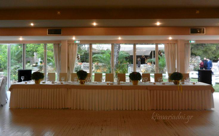 Το νυφικό τραπέζι στην αίθουσα Φαιστός διακοσμημένο με γλάστρες που έχουν μυρωδάτο βασιλικό και κηροπήγια από λεμόνια.