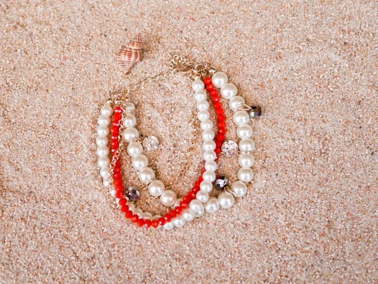 Pulsera de 4 pulseras en 1. Una cadenita dorada, una pulsera de perlas pequeñas, otra de perlas medianas con adornos brillantes que cuelgan y una de pequeños abalorios rojos imitación Swarovski muy brillantes. Cierre ajustable a tu medida.