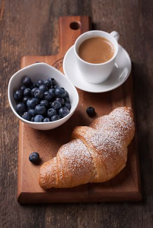 croissant with coffee and blackberries on a wooden board. Selective focus
