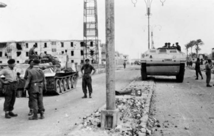 A British link up between the 3rd Battalion The Parachute Regiment and the Commandos at the Coast Guard barracks in Port Said. The paratroopers have with them a captured SU-100 tank destroyer and the Commandos a Buffalo amphibious assault vehicle.