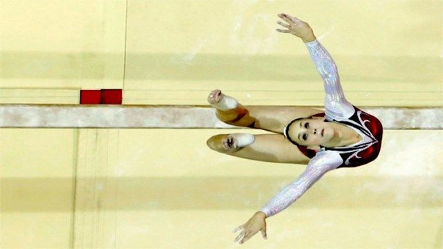 July 12, 2015 CALM BEFORE THE LANDING - The United States' Rachel Gowey soars peacefully through the air above the beam, unafraid of the grip gravity will soon have on her.
