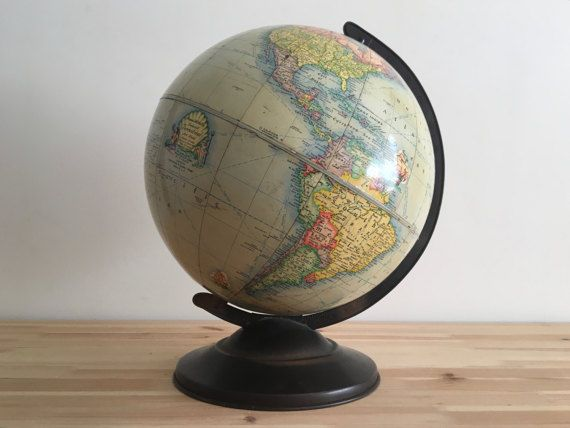 This is a 1940 Rand McNally Indexed Terrestrial Art World Globe measuring 12 inches in diameter and approximately 15 inches from top to bottom. The piece is comprised of coated paper gores with a metal base and a metal time dial at the North Pole. The globe displays historical ships including Captain Cooks Resolution, the Santa Maria, a Viking Ship, Captain Drakes Ship The Golden Hind, an Arabian Show, Magellans ship Victoria and a boat titled Chinese Junk. The oceans have an amber finish…