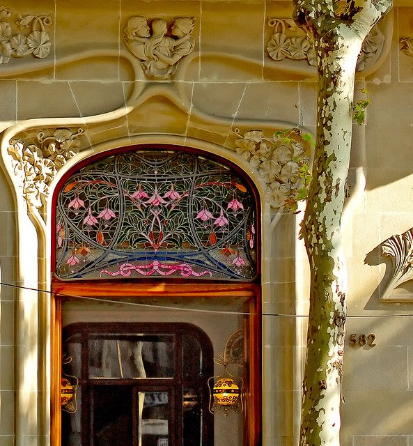 """Art Nouveau door across the street from our penthouse on Gran Via Corts Catalanes...[Barcelona],"" by mistca, via Flickr. -- Love both the stained glass above the door and the lamps!"