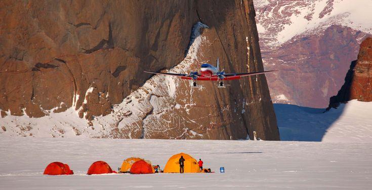Un avion survolant un camp de tente sur la banquise - croisière en Antarctique