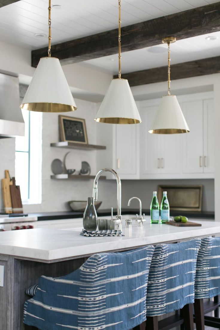 Blue upholstered barstools add a pop of color in this stylish white kitchen. Cone pendant lights with a sleek gold interior are centered above the island, and small decorative elements sit on floating shelves and countertops, adding personality without clutter.