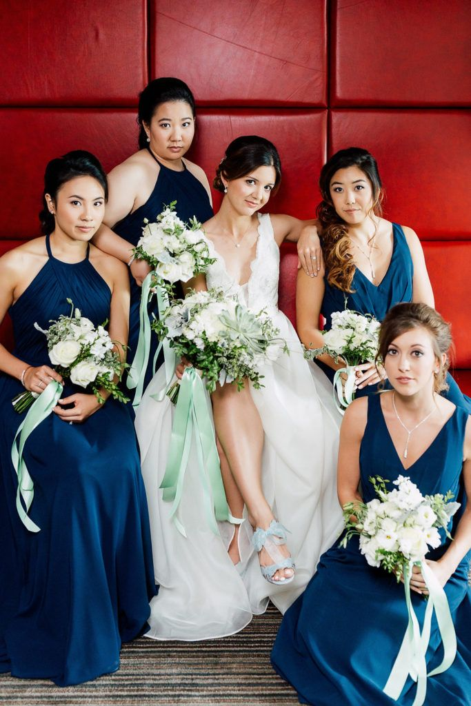 Gorgeous bridal party with navy blue dresses and organic white and green bouquets with mint green long ribbons