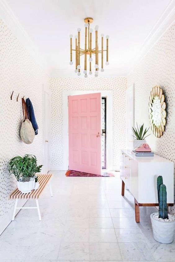 Bright midcentury Palm Springs style entryway with a pink door, brass lighting fixture, desert plants and fun wallpaper makes a major entryway statement.